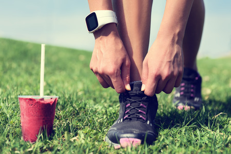 woman eating fruit: Fresh start on weight loss - runner tying laces with fruit smoothie wearing smartwatch for cardio. Detox, clean eating and diet. Woman getting ready for jogging workout. Closeup of running shoes.
