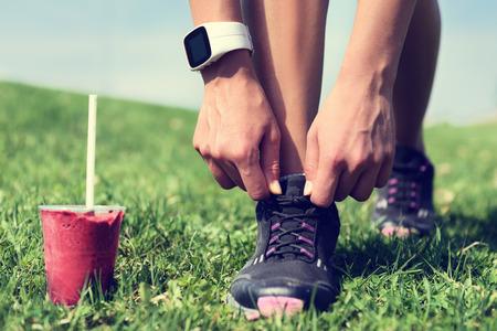 gimnasio mujeres: Un nuevo comienzo en la pérdida de peso - corredor cordones de atado con batido de frutas que lleva SmartWatch para cardio. Detox, comer limpio y dieta. Mujer que consigue listo para correr entrenamiento. Primer plano de zapatos para correr.