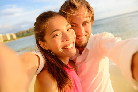 Happy multiracial couple taking fun selfie during summer vacation on Waikiki beach, Hawaii travel using smartphone camera at sunset. Young adults together, Caucasian man, Asian woman. Stock Photo