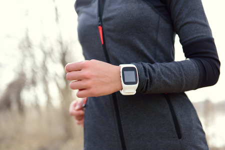 Smartwatch woman running with heart rate monitor. Closeup of female wrist wearing smart sport watch as activity tracker outdoors during cardio workout.