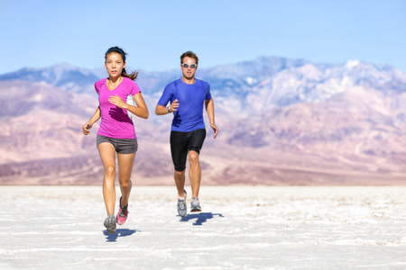 full: Runners trail running on dry desert landscape. Couple of fit athletes sprinting in compression activewear wearing sports clothing sweating in hot weather. Full length people in dramatic nature.