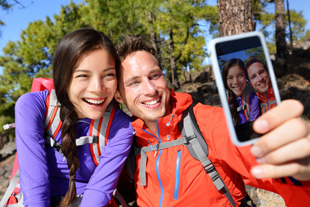 hiking: Happy friends hikers taking selfie on hiking trip. Couple posing for self-portrait picture on smartphone during summer holidays vacation travel camping and backpacking. Young multiracial couple.