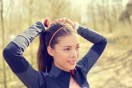 Woman tying hair in ponytail getting ready for run. Beautiful Asian young adult attaching her long brown hair on outdoor trail running path in forest to prepare for workout. Stock Photo