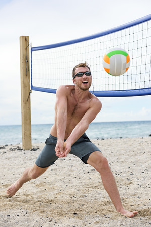 beach volleyball: Man playing beach volleyball game hitting forearm pass volley ball on summer beach. Male model living healthy active lifestyle doing sport on beach wearing sunglasses