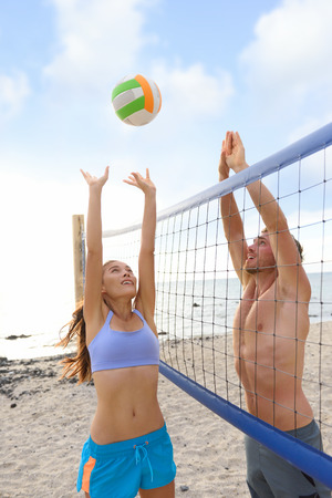 Beach volleyball sport people playing outside in summer jumping for volley ball in healthy active lifestyle. Women and men playing together having fun outdoors.