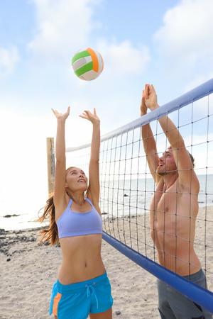 pelota de voley: Playa deportivas de voleibol gente jugando fuera en verano saltando de voleibol en el estilo de vida saludable y activo. Las mujeres y los hombres que juegan juntos divertirse al aire libre.