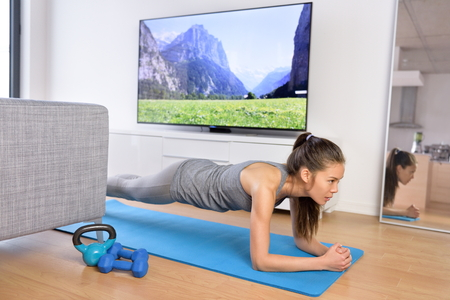 mat: Living room fitness workout - girl doing plank exercises to exercise core at home. Young Asian woman training muscles in front of the TV as part of a healthy lifestyle without going to the gym.