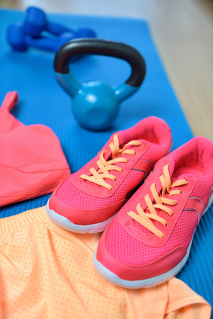 Gym shoes - Fitness outfit closeup with kettle bell. Cross fit workout clothes on yoga mat in pink neon color with weights on the floor. Fashion active wear clothes concept.