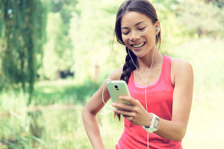 Happy young fit woman using cell phone while listening to music on smartphone.
