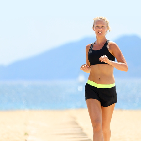 sunny: Young Caucasian woman in sportswear running at beach.  Stock Photo