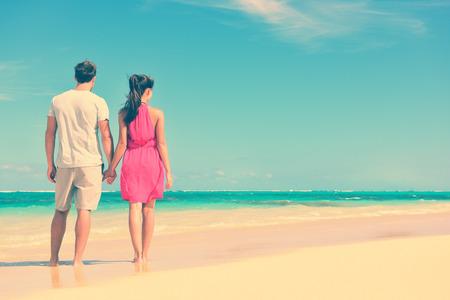 luna de miel: Pareja de pie en recorrido de la playa tomados de la mano. Foto de archivo