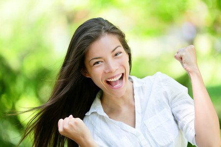 attractive people: Portrait of successful young woman with clenched fists. Attractive female is celebrating victory. She is in casuals at park.