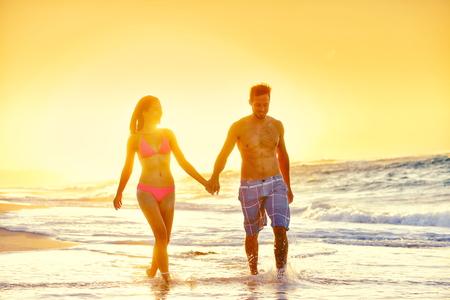 traje de baño: Pareja joven en traje de baño de pie en la playa. Mujer y hombre parejas románticas multiétnicos están tomados de la mano mientras disfruta de vacaciones de verano. Turistas cariñosos están disfrutando de la puesta de sol en la playa.