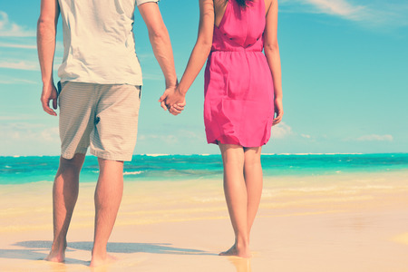 parejas enamoradas: Sección baja de pareja multiétnica de la mano en la orilla. Loving jóvenes turistas están de pie en la playa. Ellos están gastando tiempo libre juntos.