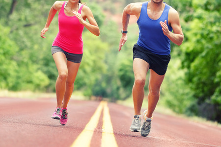 sport clothes: Low section of determined man and woman running on country road.