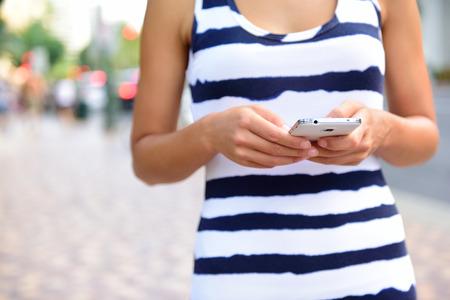 Partie médiane d'une jeune femme textos sur smartphone sur rue. Banque d'images