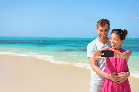 two couples: Happy young multiethnic couple taking selfie on mobile phone at beach.