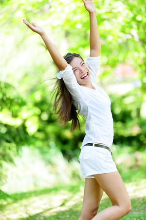 enjoyment: Excited young woman with arms raised standing in park.