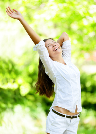 raising: Happy young woman raising arms in park.