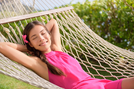 behind: Happy relaxed young woman with hands behind head lying on hammock.