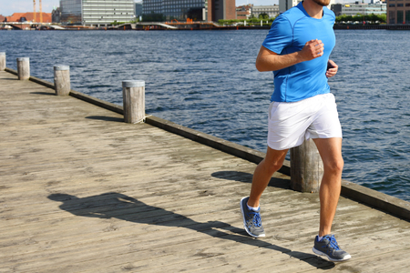 jogging in nature: Low section of fit young man jogging on boardwalk.  Stock Photo