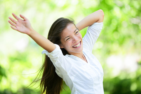 asian lifestyle: Joyful young woman raising arms in park. Attractive mixed race Asian  Caucasian female is in casuals. She is looking away while smiling.