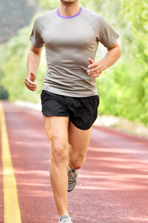 front view: Low section of determined man running on country road.