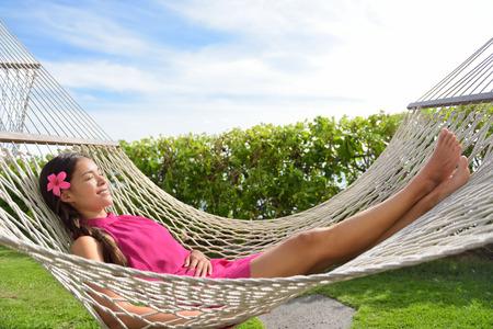 Volledige lengte van gelukkige ontspannen jonge vrouw, liggend op hangmat. Stockfoto