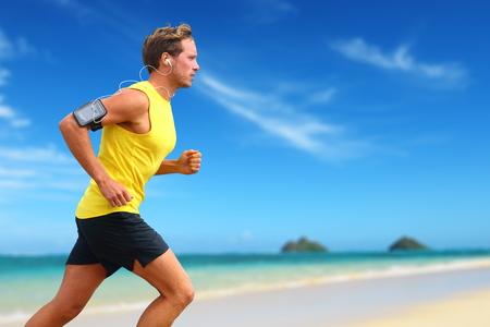 Runner smartphone luisteren muziek die op het strand. Stockfoto