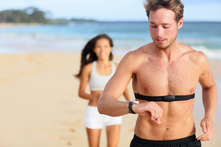 Running young man jogging on beach using heart rate monitor.  Stock Photo