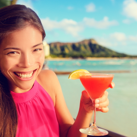 drinking alcohol: Woman drinking cocktail alcohol drinks at beach bar resort in Waikiki, Honolulu city, Oahu, Hawaii, USA.   Stock Photo