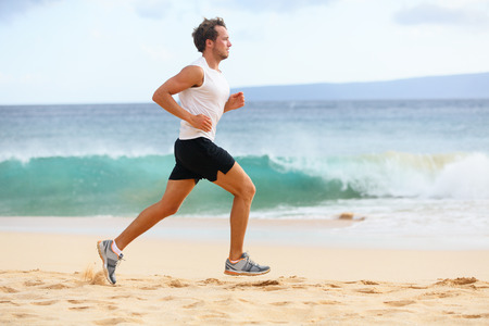 Fitness sports runner man jogging on beach. Handsome young fit sporty male athlete runni
