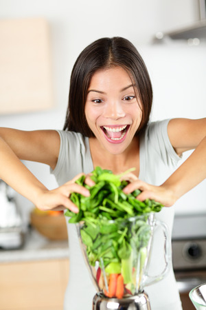 blending: Vegetable smoothie woman making green smoothies with blender home in kitchen.   Stock Photo
