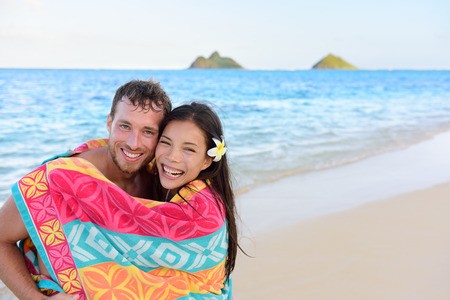 interracial love: Swimming romantic couple wrapped in bathing towel on beach.  Stock Photo
