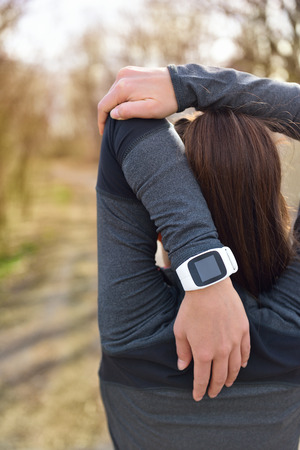 Closeup of female wrist wearing smart sport watch as activity tracker outdoors during cardio workout.