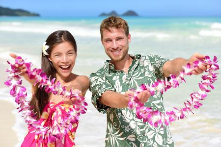 leis: Hawaiani che mostrano dando collane di fiori collane di gesto accogliente per il turismo.