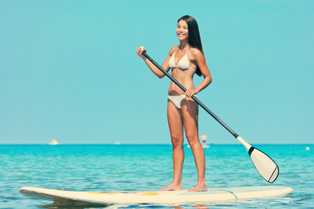 sup: Stand up paddle board woman paddleboarding on SUP on Hawaii standing happy on paddleboard on in water.   Stock Photo
