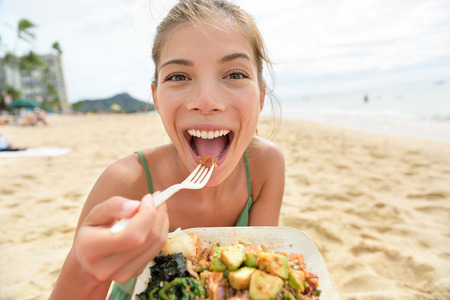 to eat: Funny woman eating salad healthy meal on beach in Hawaii.  Stock Photo