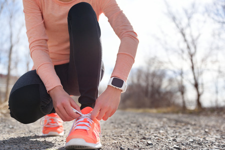 shoes woman: Running shoes and runner sports smartwatch. Female runner tying shoe laces on running trail using smart watch heart rate monitor.