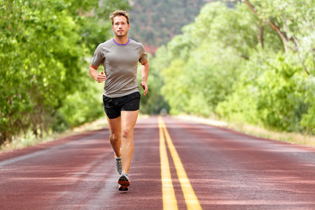 jogging: Sport and fitness runner man running on road training for marathon run doing high intensity interval training sprint workout outdoors in summer.  Stock Photo