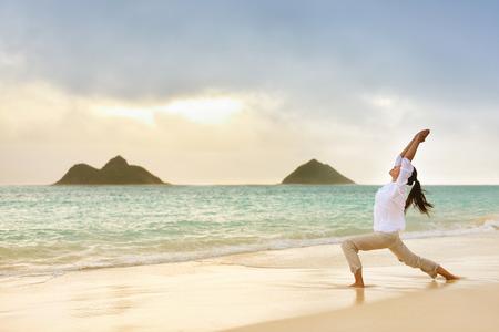 戦士ポーズ リラックスできるビーチで日の出瞑想ヨガ女性。