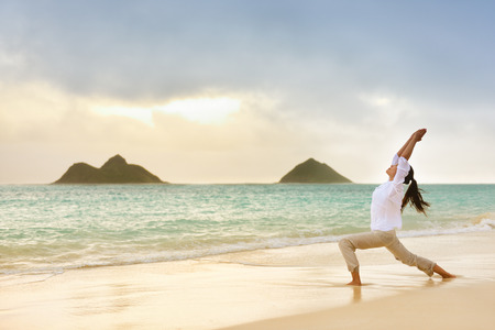 Yoga woman meditating in warrior pose relaxing outside on beach at sunrise.