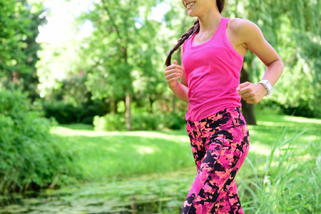 activewear: Woman runner jogging in city park. Female in activewear running living healthy active lifestyle.