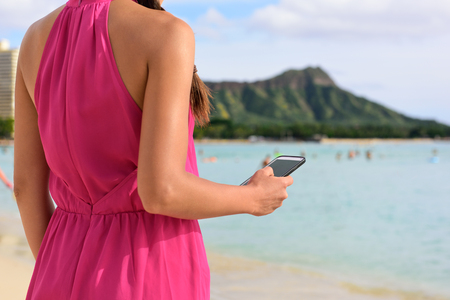 hawaii: Smart phone woman using smartphone app on Waikiki Beach. Girl sms text messaging or browsing on internet outdoors. Close up of mobile phone and model hands on Oahu, Hawaii, USA.