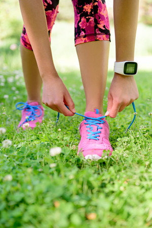 summer sport: Weight loss - runner tying laces wearing smartwatch heat rate monitor and activity tracker for cardio exercise. Woman getting ready for jogging workout. Closeup of running shoes.