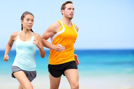 ビーチを走るランナー。健康的なアクティブなライフ スタイルを生きている完全なボディ長さのビーチでカップル トレーニングをジョギングします