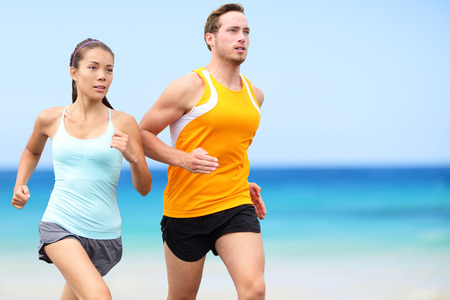 Runners running on beach. Jogging couple training on beach in full body length living healthy active lifestyle. Asian runner woman and fit male fitness athlete on run. Stock Photo