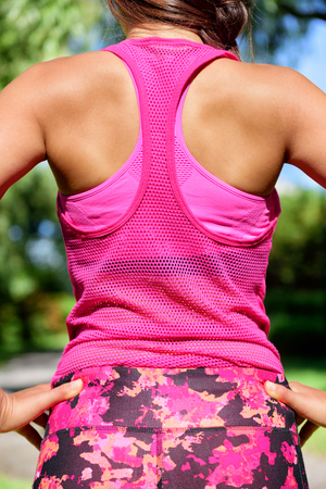 activewear: Woman runner in mesh tank top activewear and floral leggings. Female runner after workout.