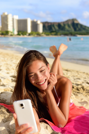 waikiki beach: Smart phone woman using smartphone app on beach smiling laughing having fun. Girl reading or messaging or browsing on internet smiling happy outdoors. Mixed race female model on Waikiki Oahu, Hawaii. Stock Photo