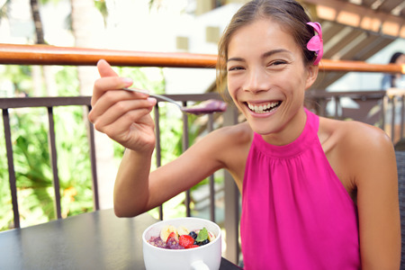 Acai bowl - woman eating healthy food smiling happy. Girl enjoy acai bowls made from acai berries and fruits outdoors for breakfast. Girl on Hawaii eating local Hawaiian dish.